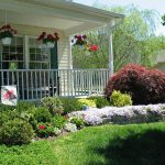 Beautiful front yard for simple ranch home with porch single wood porch chair some hanging ornamental pots with flowers vertical wood railing for porch in white paint color