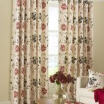 Beautiful window full length curtains with flower motifs a white sofa with flower motif pillow wood table with glass vase for decorative fresh flowers
