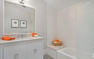 Beveled subway tile sizes for shower ideas in bathroom with modern bathroom vanity units and large mirror and wall scone on it