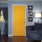 Bright yellow door grey corner chair some picture frames a standing lamp grey window curtains with tied ribbon darker stained wood planks flooring