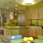 Casual kitchen idea in green theme with  bright green acrylic tiles for backsplash green surface kitchen island  green and blue dining chairs  simple modern pendant lamps wood kitchen storage system
