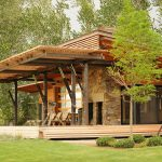 Dominant wood construction as energy efficient home with natural stones and wooden wall system
