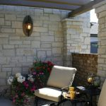 Fond du lac stones for wall and pillars constructions a pair of chairs with black metal wire side table a group of decorative flowers single wall lighting