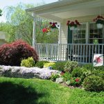Front yard landscape idea for ranch home with porch furniture and hanging plants as the decorations
