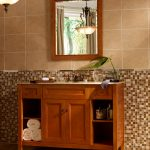 Half way tiles for bathroom wall that consists of mosaic tiles and cream tone color ceramic tiles a wood bathroom vanity with single sink and brushed copper faucet a decorative mirror with wood frame