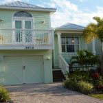 Key West home exterior design with balcony garage and small front porch