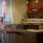 Luxurious home wine bar design with wood wall system and wood shelf for wine bottle collections two barstools with backrest