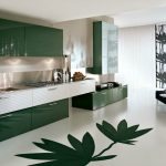 Modern minimalist kitchen design in green theme with decorative green leaves on floor green kitchen cabinet systems white kitchen drawers white surface countertop and dark blue chair