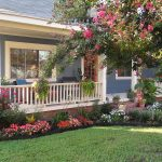 Simple landscape idea for front yard of ranch home design with porch wood railing for porch and porch furniture
