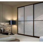 Sliding door with shoji panels and black wood trims in bedroom white mattress black standing lamp