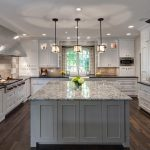 Transitional kitchen idea with granite top kitchen island dark granite surface kitchen counter darker wood stain flooring attractive pendant lamps
