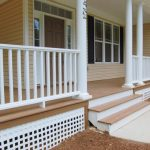 a front porch for semi modern ranch style home white paint vertical wood railing system and concrete pillars for porch and low outdoor stairs no railings