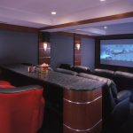 a private home theater with large flat screen black leather sofas unique and stylish red chairs bar table modern lighting fixtures mounted on wall