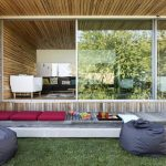 a verandah with wood planks floors red mattress cool and simple outdoor chairs a sliding glass door