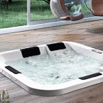 adorable modern built in hot tub design in white with black backrests and wooden patio deck with hanging egg glass chairs
