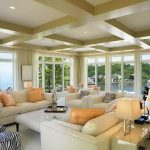 adorable soft luxurious florida roomd design with white sofa and orange cushions and storage with table lamps and textured ceiling with lighting and open plan