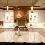amazing cream kitchen design with white cabinetry design and wooden accent of the smokestack and large kitchen island with seating beneath double yellowish pendants with white marble countertop