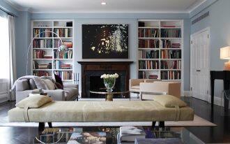 amazing large white built in bookshelves idea with black fireplace design in living room with cream sofa design with bench and bay window design