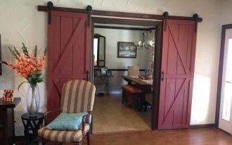 amazing red barn door design with black rustic metal rod idea with stripe patterned seating aside flower decoration upon laminated flooring style