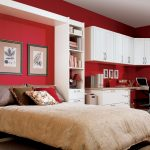 amazing red fold up wall bed design with cream quilt and wall picture between standing wall racks and white desk and upper cabinet