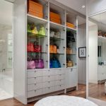 amazing white and tall handbag storage idea with glasss racks and colorful boxes and white drawers and round puff