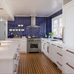 an example of kitchen design in modern style with bright blue ceramic tiles backsplash and white storage system a kitchen island in white whit storage floating dishware rack pendant lamps