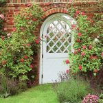 arched white lattice fence design around reddish brick wall with beautiful flower decoration with meadow grass