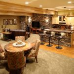 basement bar in rustic style small bar table with natural stone base construction three barstools in black small kitchen counter with storage a media console with TV set a brown leather sofa
