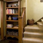 basket weave carpet in home stairs plus classic wooden bookshelf plus wall scone and hardwood flooring