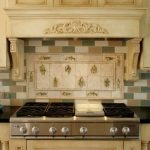 beautiful moaic long tiles with groutless backsplash idea beneath golden white cabinetry above modern cooktop idea upon black glossy marble countertop