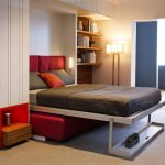 bed that folds into wall for space saving bedroom ideas combined with wooden wall mounted bookshelf plus red sofa beneath plus standing floor lamp and rug flooring