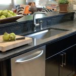 best kitchen sink material and modern faucet plus black wooden cabinets and also granite countertops plus fresh fruits and wooden floor