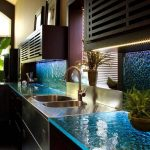 best kitchen sink material in double steel sinks plus faucet and blue glass countertop plus greenery