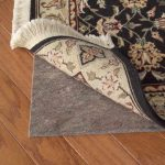 best rug pads for hardwood floors from natural fiber in home interior placed under black rug  with floral motif