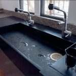 black soapstone countertop design with glass window and modern sink and faucet and wire basket