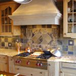 blue tiles backsplash for kitchen with rustic white cabinetry idea beneath giant smokestack and bathed with modern lighting