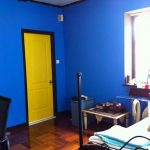 bright blue wall color paint for bedroom wood door in yellow color vinyl floors look like wood floors black metal bed furniture