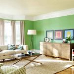 bright  green color paint for wall soft grey window curtains   white sofa with beautiful pillows  a red chair a green chair minimalist credenza furniture  wood floors tiny legs standing lamp