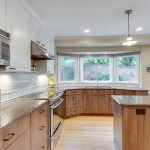 bright kitchen remodeling northern va in white painted wall and wooden cabinets plus glass bow windows and granite countertops plus wooden flooring