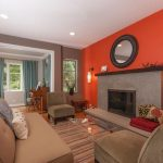 bright orange color for walls round mirror modern built in fireplace mantel brown sofa and a pair of darker brown corner chairs  brown rug full transparent glass table a pair of modern wall laighting