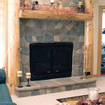 broken stone fireplace design with sloping design with cedar decoration with accessories above black frame with blue seating with round wooden coffee table
