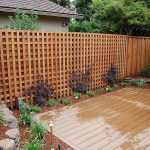 brown natural wooden lattice fence design with tall shape with wooden deck patio with seating and small garden with stone decoration