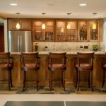 classic basement bar design with natural brown barstools marble top bar table a countertop with floating cabinets system with transparent glass door some pendant lighting fixtures