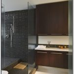 classic bathroom design with wooden cabinetry with white countertop and walk in shower with mosaic casa antica tile