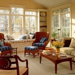 classic room style with bench under window furniture a pair of wood chairs with blue stripes seat feature a white sofa with black pillows a square wood table two built in shelves