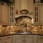 classic white kitchen design with back soapstone countertop with creamy mosaic casa antical tile and cabinet lighting
