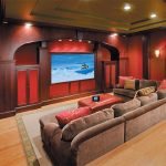 comfortable and stylish private home theater design with brown sectional velvet sofas with brown and red pillows unfinished wood floors