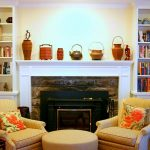 comfortable yellowish sofa design with round table before black concrete fireplace with storage with built in bookshelves