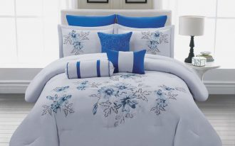 comforter with flower motifs in blue as the bedding a white round bedside table a table lamp with white cap white wood planks floors