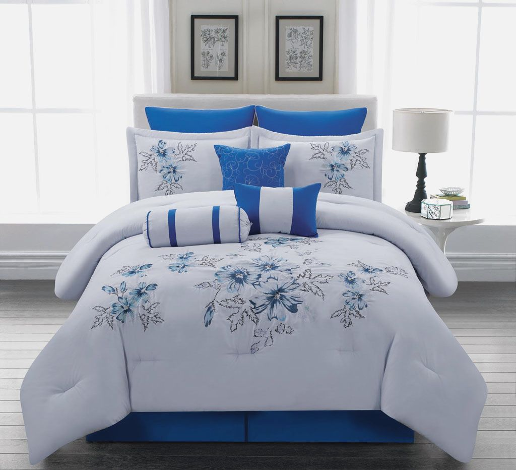 Comforter With Flower Motifs In Blue As The Bedding A White Round Bedside  Table A Table